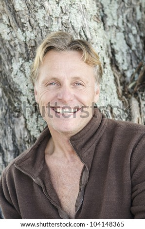 A happy smiling mature man with blond hair looking at the camera - stock photo