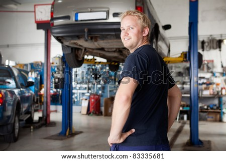 A happy smiling mechanic in an auto repair shop, looking at the camera - stock photo