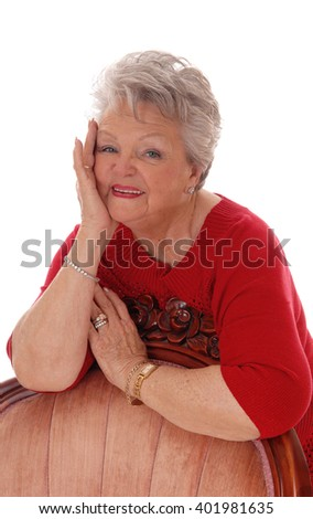A happy smiling senior woman leaning over a armchair with one handon her face, isolated for white background. - stock photo