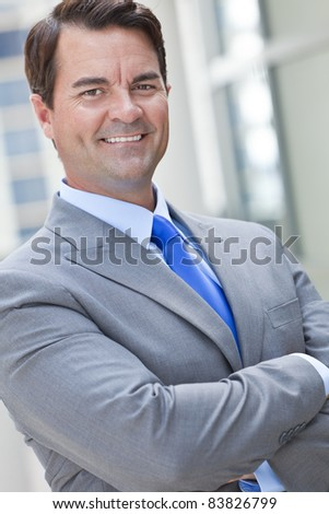 A happy, smiling, smart businessman or man outside in suit, shirt and blue tie with his arms folded - stock photo