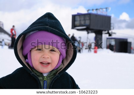 A happy smiling two uear old girl at ski resort at lake Tahoe, Sierra Nevada, California. - stock photo