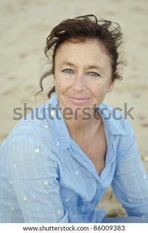 A happy smiling woman in her forties sitting on the beach wearing a blue blouse.