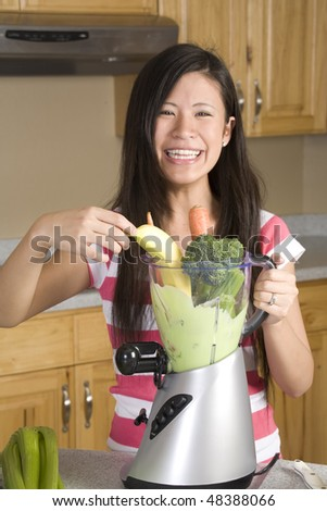 A happy smiling woman making a vegetable fruit smoothie with a huge blender full of fruit and vegetables. - stock photo