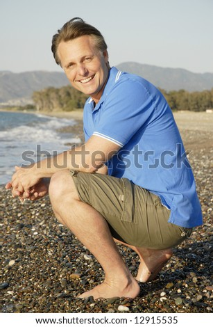 A happy smiling 44 year old man on beach. - stock photo