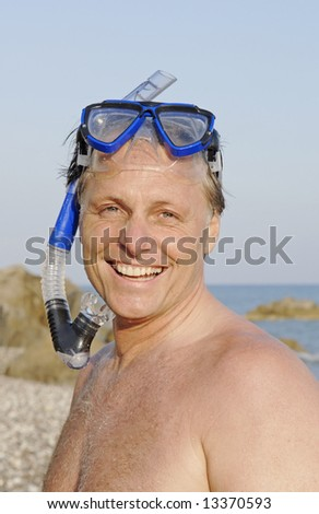 A happy smiling 44 year old man wearing mask and snorkel enjoying his beach holiday.