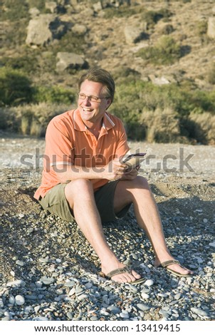 A happy smiling 44 year old man wearing spectacles is reading book on beach. - stock photo