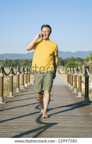 A happy smiling 44 year old walking and talking on phone.