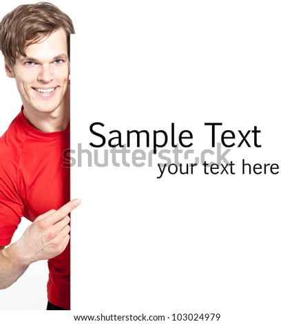 A happy smiling young man pointing at advertisement - much space for own text - stock photo