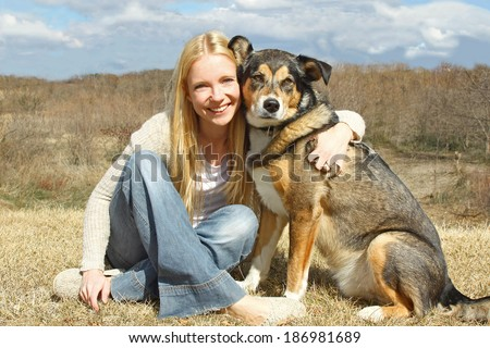 a happy, smiling young woman and her large German Shepherd Dog are sitting outside in the country, hugging. - stock photo