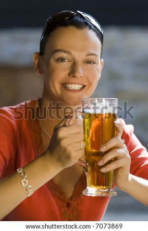 A happy smiling young woman drinking a large glass of beer