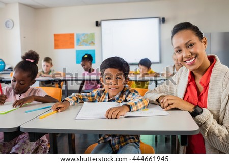 A happy teacher posing with a pupil in classroom - stock photo