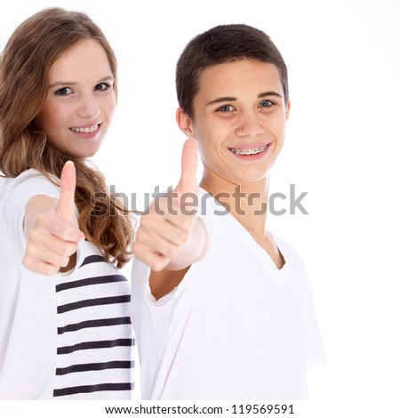 A happy teenage boy and girl giving a thumbs up on success and approval isolated on white