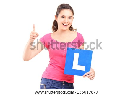 A happy teenager holding L plate and giving a thumb up isolated against white background