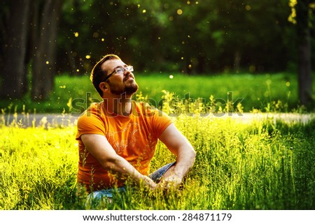 A happy thoughtful dreamer man is sitting on green grass in a park at sunny summer day and looking into future. Concept of relaxation, wellbeing, lifestyle. - stock photo