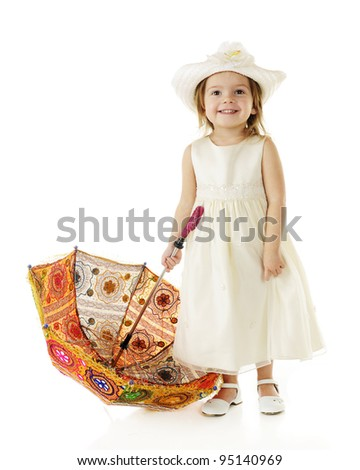 A happy, toddler dressed on in white, holding on to the handle of her multicolored parasol which has its top resting on the ground.  On a white background. - stock photo
