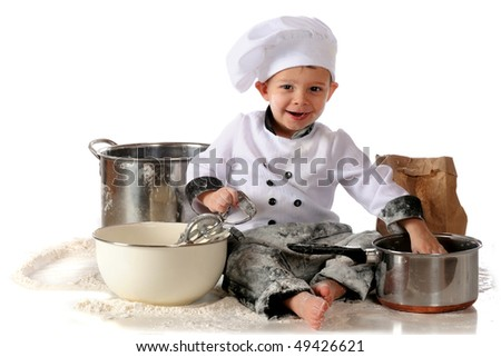 A happy toddler in a chef's outfit, sitting among kitchen utensils and spilled flour.  Isolated on white. - stock photo