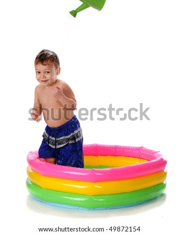A happy toddler in a kiddie pool getting doused by a watering can.  Isolated on white. - stock photo