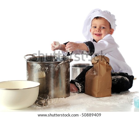 A happy toddler in chef's clothing adding a fistful of flour to a cooking pot.  Isolated on white. - stock photo