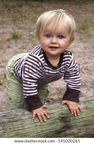 A happy toddler wants to stand up and start to walk. Vertical. Happy feeling