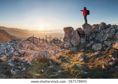 A happy traveler on a mountain top looking ahead. Shows his hand toward the horizon - stock photo