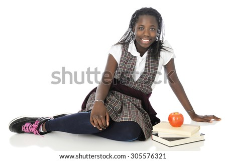 A happy tween schoolgirl relaxed on the floor in her school uniform, a small stack of books by her side.   On a white background. - stock photo