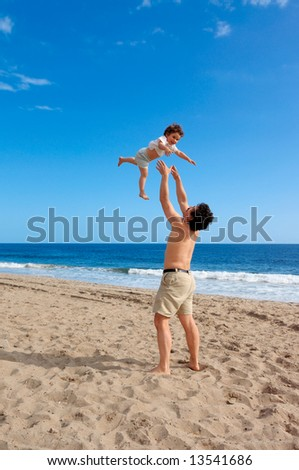 A happy two and a half year old girl tossed into the air on a summer beach at Point Mugu State Park, California - stock photo