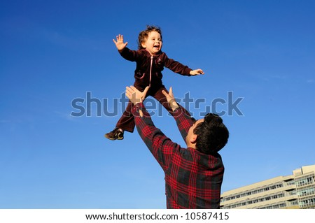 A happy two year old girl tossed into the blue sky by her father. - stock photo