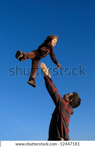 A happy two year old girl tossed into the blue sky by her father (portrait (vertical) orientation).
