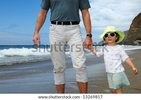 A happy two year old girl with a grimy face after playing with the family's barbeque holds man's hand on a beach at Point Mugu State Park, California - stock photo