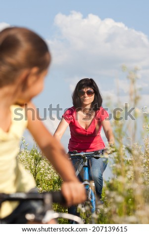 A happy woman and child, mother and daughter, cycling together on the meadow - stock photo