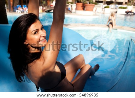 A happy woman going down a water slide - stock photo