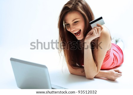 A Happy Woman holding a credit card and shopping from the internet - stock photo