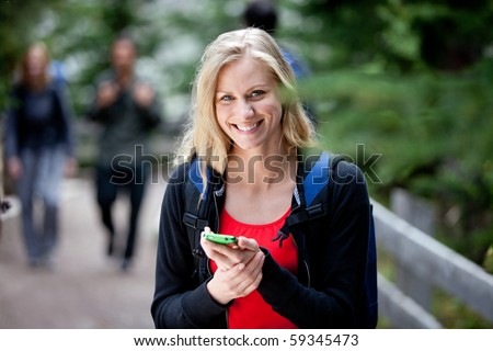 A happy woman holding a smart phone, looking at the camera