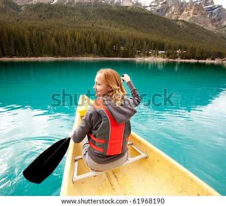 A happy woman in a canoe on a clear glacial lake - stock photo