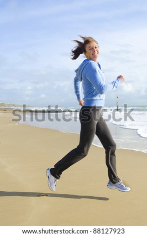 A happy woman in her forties jogging on a beautiful sandy beach and wearing a blue hooded top. - stock photo