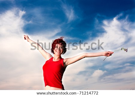 A happy woman in red holding a flower, on the backdrop of blue sky.