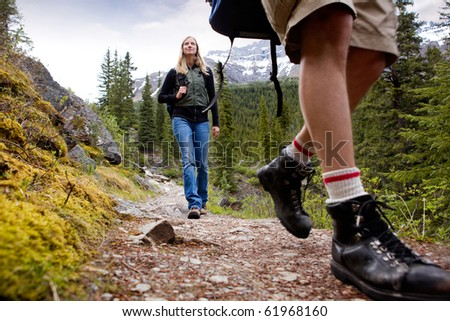 A happy woman on a mountain trail with mountains in the background - stock photo
