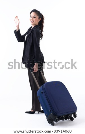 A happy woman pulling her luggage and waving her hand to good bye her family