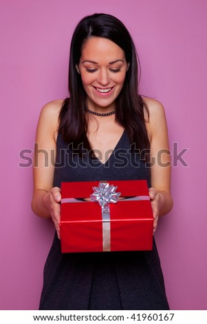 A happy woman receiving a christmas or birthday or anniversary gift. - stock photo