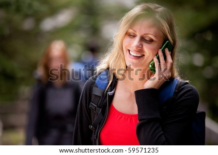 A happy woman talking on a cell phone outdoors