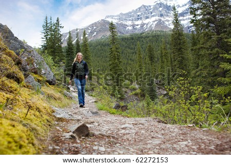 A happy woman walking on a path on a mountain hike in Banff National Park - stock photo