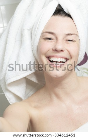 A happy woman with towel on his head on bathroom. - stock photo