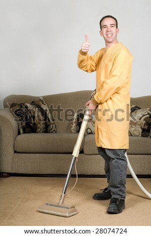 A happy worker cleaning the carpets and giving the camera a thumbs up - stock photo