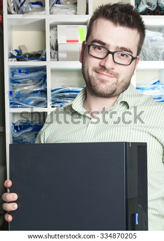 A happy worker technician at work with computer. - stock photo