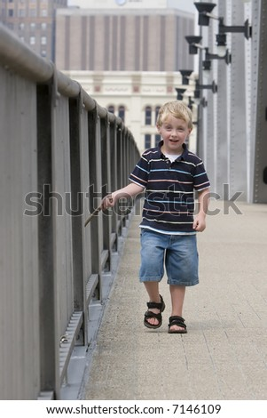 A happy 4 year old boy walking along a bridge and striking the bridge railing with a stick - stock photo