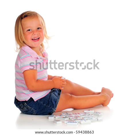 A happy 2 year-old playing with white dominoes.  Isolated on white. - stock photo