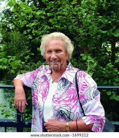 A happy 85 year old senior lady on a Sunday afternoon stroll in the park - stock photo