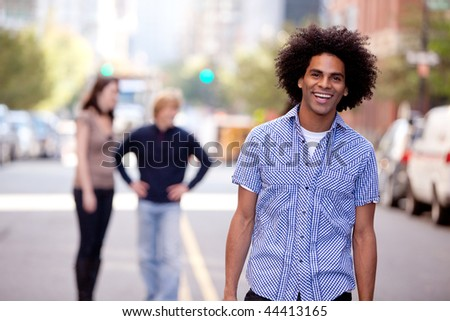 A happy young adult in a city setting with friends - stock photo