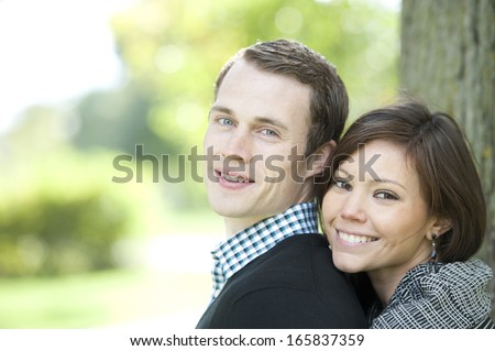 A happy, young and attractive couple looking at the camera on a sunny day at a park