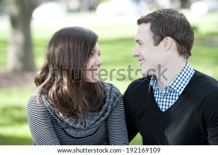 A happy, young and romantic couple looking into each others eyes on a sunny day. - stock photo
